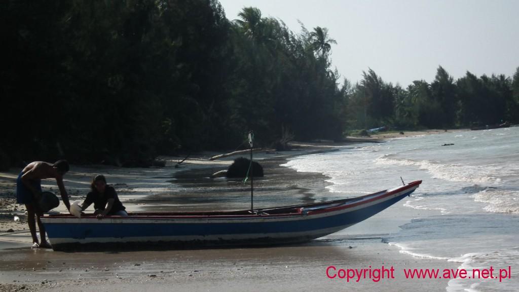 Tajowie przygotowyjący niewielką łódz do wypłynięcia w morze.